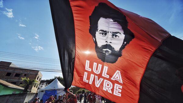 Un apoyador del expresidente de Brasil, Luiz Inácio Lula da Silva, ondea una bandera con la imagen de da Silva y un mensaje que dice Lula libre - Sputnik Mundo