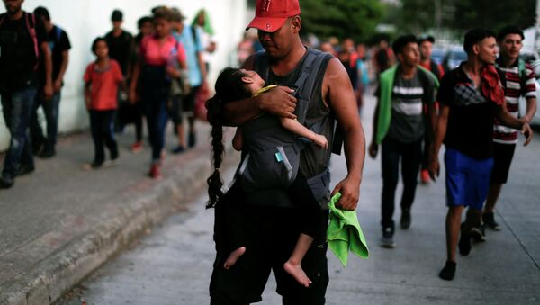 Hondureños que forman parte de una caravana de inmigrantes que se dirige a Estados Unidos caminan por Tapachula, México - Sputnik Mundo
