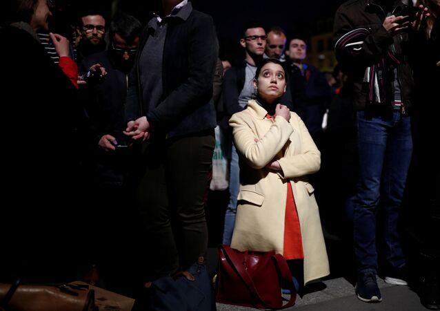 Una mujer se pone de rodillas entre la multitud que observa consternada el incendio de Notre Dame