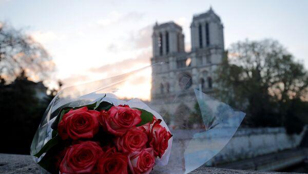 Un ramo de flores cerca de la catedral parisina de Notre Dame - Sputnik Mundo