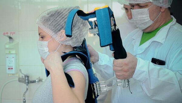 Una endocirujana se prepara para una operación con el exoesqueleto de fabricación rusa - Sputnik Mundo
