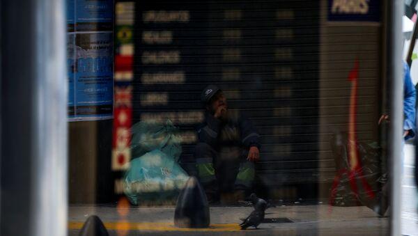 El reflejo de un hombre pidiendo limosna en la vidriera de un cambio de Buenos Aires - Sputnik Mundo