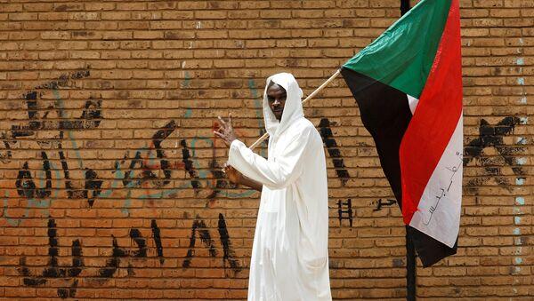 Un hombre con la bandera de Sudán - Sputnik Mundo