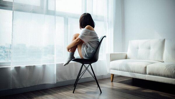 Una mujer mira por la ventana  - Sputnik Mundo