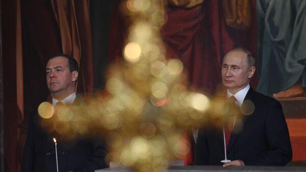 El primer ministro ruso, Dmitri Medvédev, y el presidente de Rusia, Vladímir Putin, durante la misa de Pascua en Moscú - Sputnik Mundo