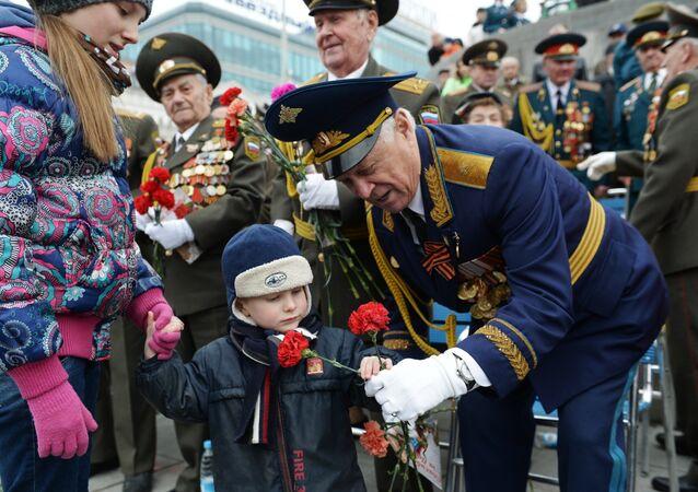 Un niño regala claveles rojos a un veterano durante las celebraciones del Día de la Victoria de 2017, en el Parque de la Victoria en Moscú