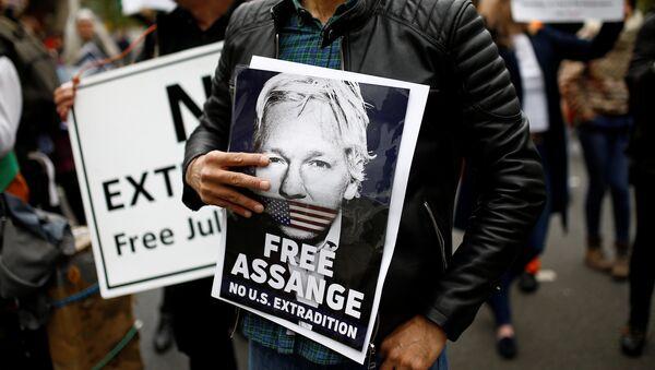 Una persona con un retrato de Julian Assange - Sputnik Mundo