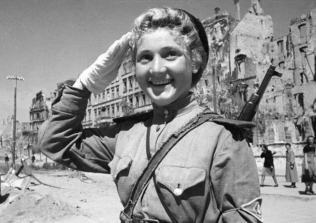 A las 2:10 del 9 de mayo de 1945, el locutor soviético Yuri Levitan leyó el Acta de Entrega Militar de la Alemania Nazi y el Decreto del Presídium del Sóviet Supremo de la Unión Soviética anunciando el 9 de mayo como el Día de la Victoria. En la foto: una controladora de tráfico en las calles de Berlín.