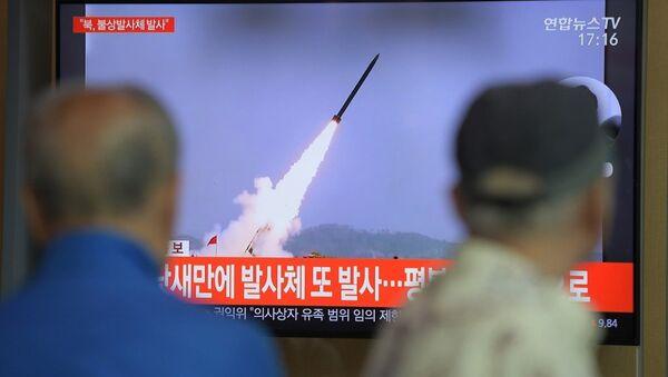 Ciudadanos de Seúl ven un programa de televisión que muestra imágenes de archivo de los proyectiles lanzados por Corea del Norte - Sputnik Mundo