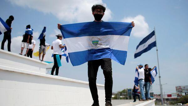 Un hombre con la bandera de Nicaragua - Sputnik Mundo