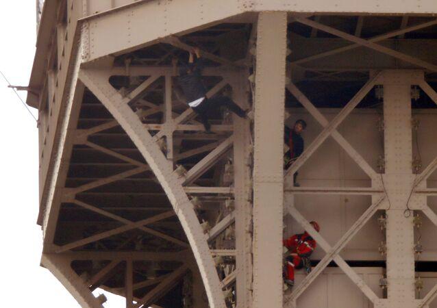Un hombre intenta escalar la Torre Eiffel