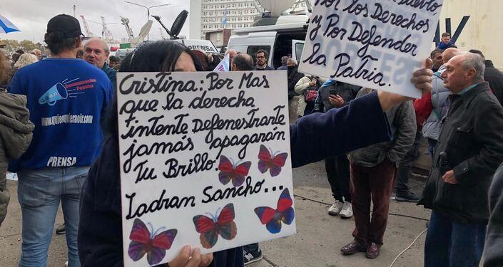 Mujer sostiene carteles en apoyo a Cristina Fernández fuera de tribunales