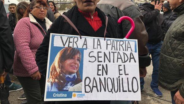 Una mujer sostiene un cartel en apoyo a Cristina Fernández durante el juicio oral en su contra - Sputnik Mundo