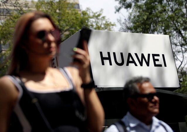 Personas pasando cerca de un cartel de Huawei en Ciudad de México