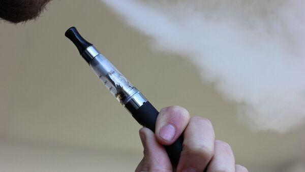 Una persona fumando un cigarrillo electrónico   - Sputnik Mundo