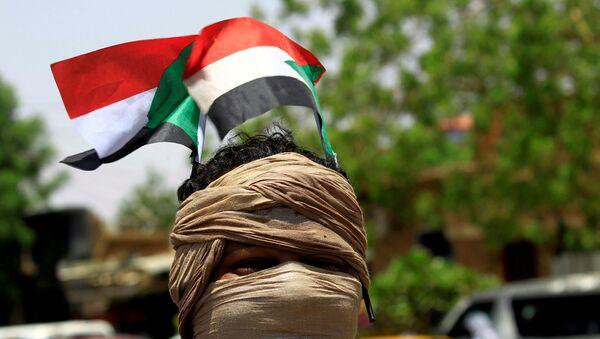 Un manifestantes con la bandera de Sudán (archivo) - Sputnik Mundo