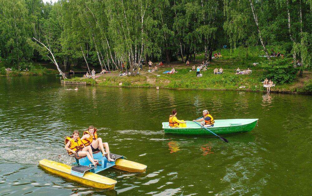 Moscovitas en barcos y catamaranes en un estanque del parque Tropariovo.