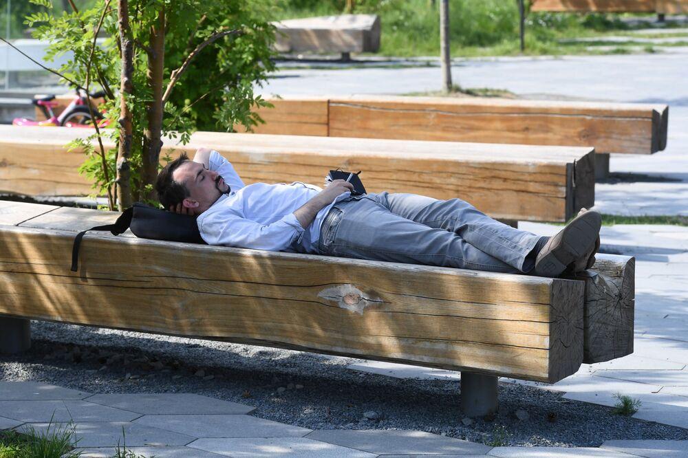 Un hombre descansa en el parque Zariadie.
