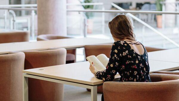 Una joven lee un libro - Sputnik Mundo