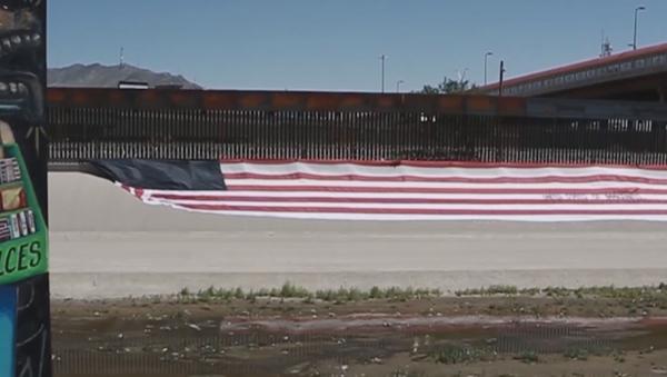 Un estadounidense despliega una bandera de ''Estados Unidos de Migrantes'' - Sputnik Mundo