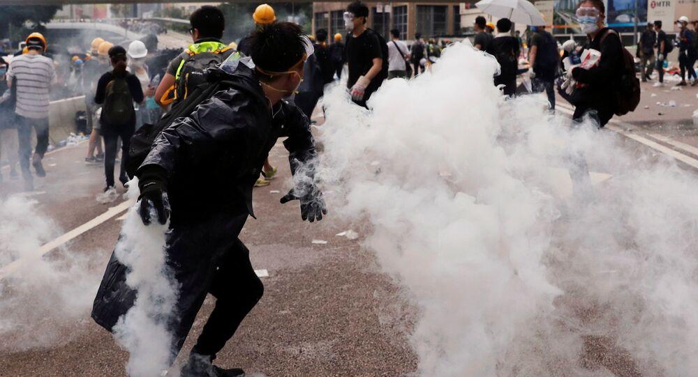 Un manifestante lanza una lata de gas lacrimógeno durante una manifestación contra un proyecto de la ley de extradición en Hong Kong, China.
