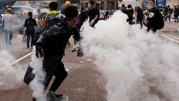 Un manifestante lanza una lata de gas lacrimógeno durante una manifestación contra un proyecto de la ley de extradición en Hong Kong, China.  - Sputnik Mundo
