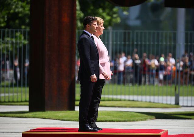 La canciller alemana, Angela Merkel, y el presidente ucraniano, Volodímir Zelenski, escuchan himnos nacionales