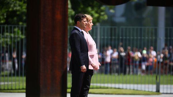 La canciller alemana, Angela Merkel, y el presidente ucraniano, Volodímir Zelenski, escuchan himnos nacionales - Sputnik Mundo