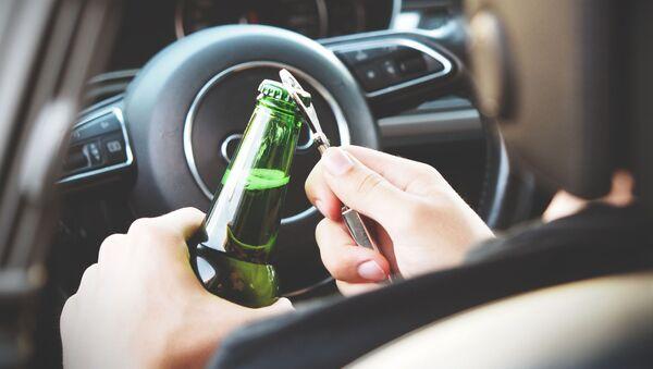 Persona abriendo una botella de alcohol en un auto - Sputnik Mundo