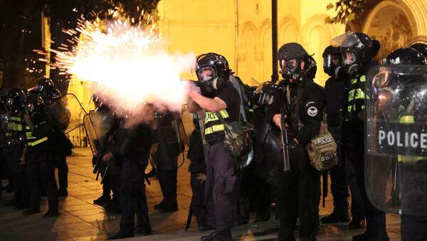 Un policía dispara durante las protestas en Tiflis, Georgia - Sputnik Mundo