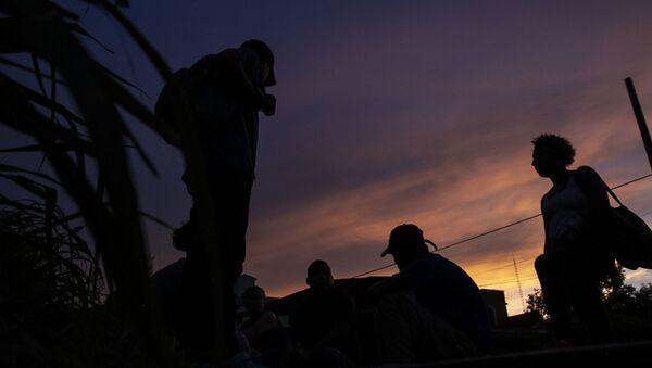 Migrantes esperan la llegada del tren apodado 'La Bestia' para viajar a los EEUU - Sputnik Mundo