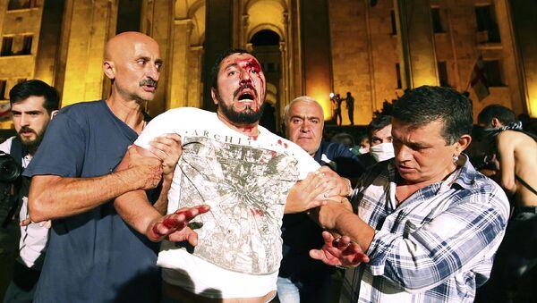 Manifestantes ayudan a un hombre herido durante las protestas en Tiflis - Sputnik Mundo