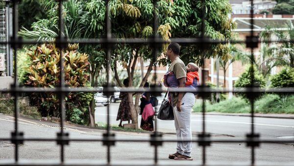 Una mujer sudafricana con su niño en busca de refugio (imagen referencial) - Sputnik Mundo