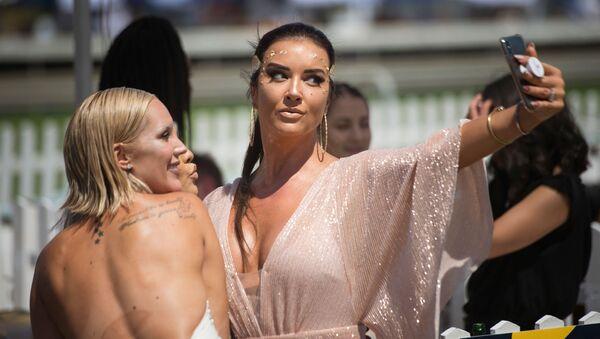 Las mujeres hacen una selfi antes del comienzo de las carreras Met horse race en Ciudad del Cabo, Sudáfrica - Sputnik Mundo