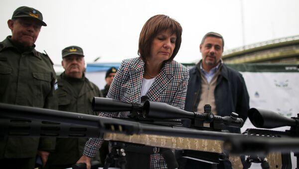 Ministra de Seguridad argentina Patricia Bullrich inspecciona un arma de fuego durante un acto - Sputnik Mundo
