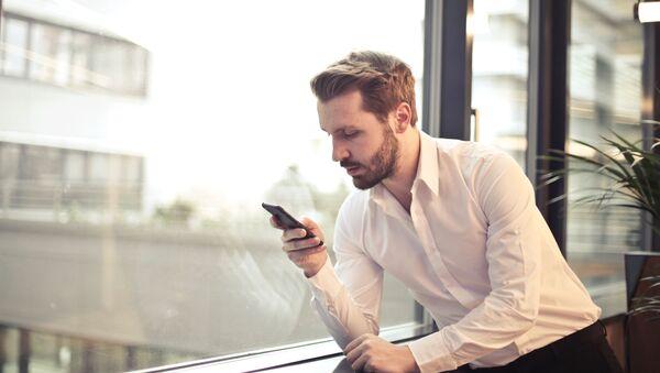 Un hombre con su teléfono móvil - Sputnik Mundo