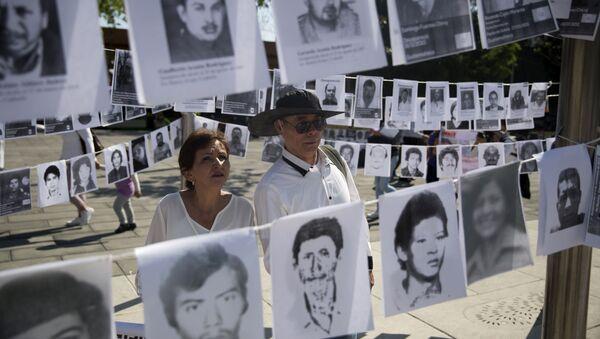 Una pareja mira las imágenes de personas desaparecidas - Sputnik Mundo
