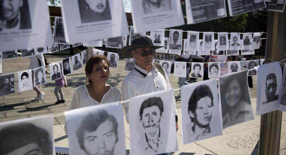 Una pareja mira las imágenes de personas desaparecidas