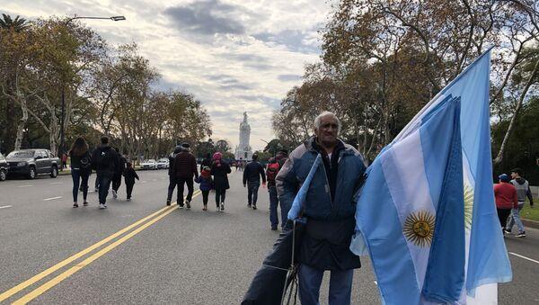 Un hombre vende banderas en la Avenida Libertador en el Día de la Independencia de Argentina - Sputnik Mundo