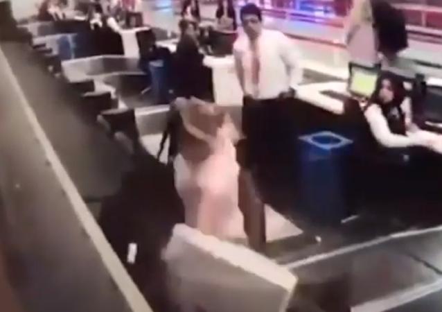 Una mujer intenta embarcarse en un avión por la cinta para facturación de equipajes