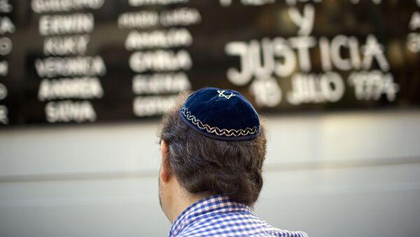 Un hombre junto a la sede de la Asociación Mutual Israelita Argentina en Buenos Aires - Sputnik Mundo
