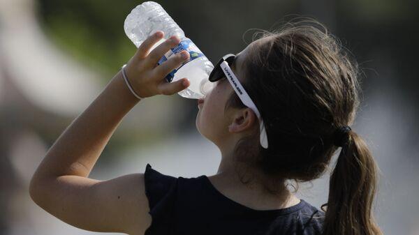 Una joven bebe agua durante la ola de calor que azotó Europa el verano de 2019 (archivo) - Sputnik Mundo