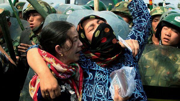 Dos mujeres uigures en frente de los policías chinos en la provincia de Sinkiang - Sputnik Mundo