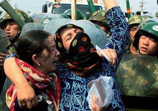 Dos mujeres uigures en frente de los policías chinos en la provincia de Sinkiang