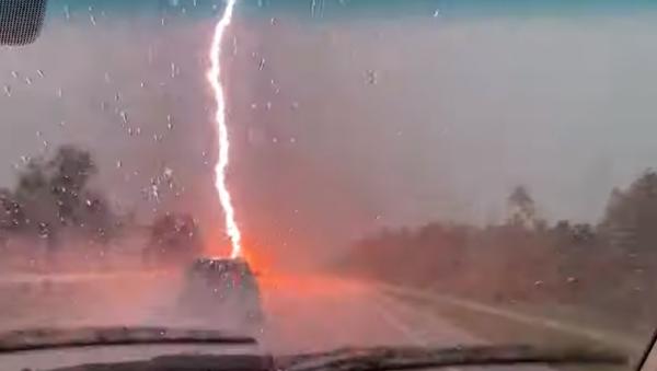 ¡Y se rompió el cielo! Un potente relámpago casi impacta en un auto en EEUU  - Sputnik Mundo