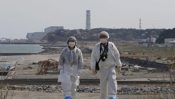 Personas en trajes de protección cerca de la planta nuclear Fukushima 2 - Sputnik Mundo