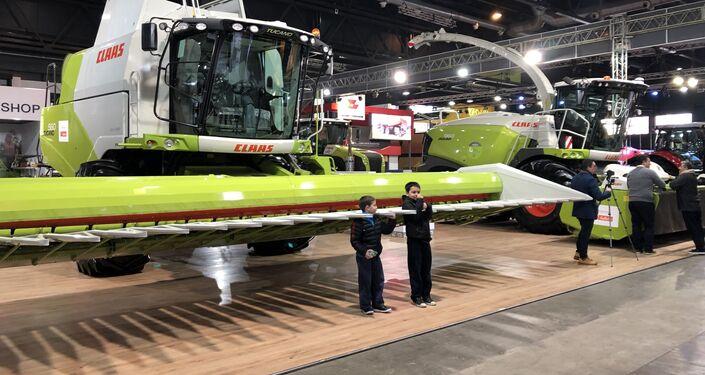 Niños admiran la maquinaria agrícola expuesta en la Exposición Rural de Buenos Aires