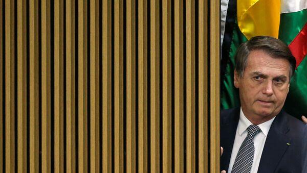 El presidente de Brasil Jair Bolsonaro observando algo desde atrás de una pared - Sputnik Mundo