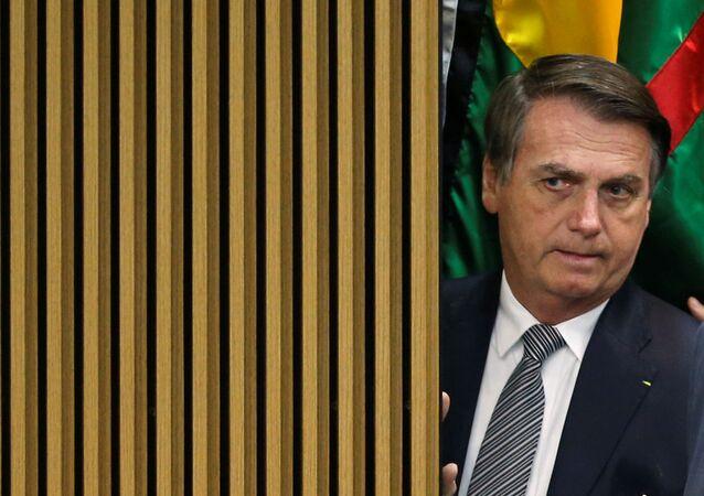 El presidente de Brasil Jair Bolsonaro observando algo desde atrás de una pared