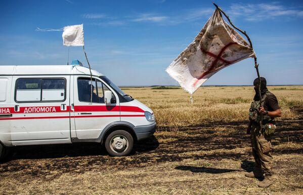 Украинский военный с белым флагом во время передачи убитых на нейтральной территории вблизи поселка Диброво в Донецкой области - Sputnik Mundo